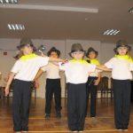 Na scenie stoją dzieci ubrane w spodnie, białe podkoszulki i kapelusze. Na szyjach żółte chusteczki