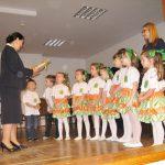 Na scenie dzieci stoją w rzędzie za nimi opiekunka przed - kanclerz wręczająca podziękowania