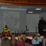 Prof. Błasiak w trakcie wykładu, widoczny ekran z prezentację
