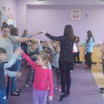 Studentki i przedszkolaki podczas zabawy. Wszyscy stoją w parach trzymają się za uniesione do góry ręce