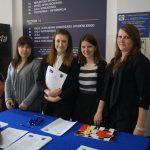 Studentki stoją za stołem do rejestracji