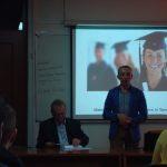 Mgr Radosław Pyrek podczas prezentacji oferty MWSE, przy biurku wykładowcy siedzi prof. Leszek Kozioł, w tle prezentacja multimedialna