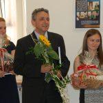Troje studentów dziękuje komisji egzaminacyjnej. Mężczyzna (w środku) trzyma kwiat słonecznika, kobiety (po bokach) trzymają kosze prezentowe