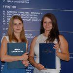 Dwie studentki stoją z pracami licencjackimi, w tle tablica informacyjna