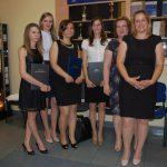 Grupa studentek pozuje do zdjęcia z pracami dyplomowymi