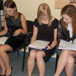 Trzy studentki siedzą na krzesłach przed aulą, przygotowując się do egzaminu dypolomowego