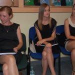 Trzy studentki siedzą na krzesłach przed aulą w oczekiwaniu na egzamin dyplomowy