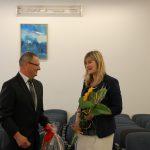Dziekan dr Renata Smoleń rozmawia ze studentem, w ręku trzyma bukiet kwiatów