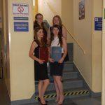 Cztery studentki pozują na schodach, prezentując prace dyplomowe