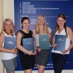 Cztery studentki pozują przed tablicą informacyjną prezentując prace dyplomowe