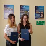 Dwie studentki stoją prezentując prace magisterskie