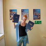 Studentka stoi, w obydwu rękach wysoko uniesione prace magisterskie
