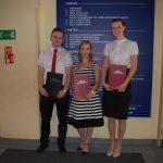 Troje studentów stoi prezentując prace dyplomowe