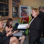 Studentki w oczekiwaniu na egzamin, dwie osoby siedzą kilka stoi, niektórzy maja otwarte prace dyplomowe