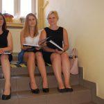 Trzy studentki siedzą na schodach w oczekiwaniu na egzamin dyplomowy