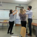 Warsztaty coachingowe, dwie kobiety i mężczyzna przypinają do tablicy planszę