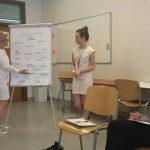 Warsztaty coachingowe, dwie kobiety stoją przy tablicy z planszą