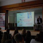 Sala wykładowa, w głębi na scenie prof. Błasiak obok ekranu z prezentacją multimedialną