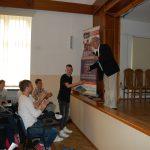 Prof. Błasiak stoi na scenie, pod sceną stik uczeń, inni siedzą na krzesłach