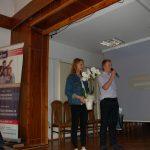 Uczennica i uczeń dziękują za wykład, dziewczyna trzyma doniczkowy storczyk
