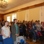 Uczniowie stoją na sali wykładowej podczas podziękowań składanych prelegentowi