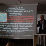 Prof. Błasiak na scenie, obok ekran z prezentacją