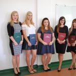 Pięć studentek - stoją obok siebie prezentując prace dyplomowe