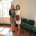 Dwie studentki stoją w sali po obronie. w rękach oprawione prace dyplomowe