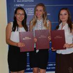 Trzy studentki prezentuję oprawione prace dyplomowe, w tle tablica informacyjna MWSE