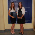 Dwie studentki z pracami dyplomowymi, w tle tablica informacyjna MWSE