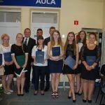 Grupa studentów pozuje do zdjęcia z pracami dyplomowymi