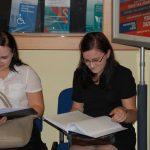 Dwie studentki w oczekiwaniu na egzamin przeglądają prace dyplomowe