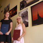 Dwie studentki stoją na schodach prezentują prace syplomowe