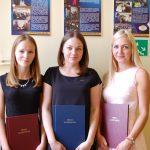 Trzy studentki stoją obok siebie przed sobą trzymają prace licencjackie