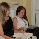 Dwie studentki siedzą w korytarzu przed aulą - czytają notatki