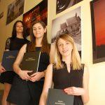 Trzy studentki stoją na schodach prezentując prace dyplomowe