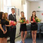 Studenci podczas ogłoszenia wyników egzaminu dyplomowego. Trzy studentki trzymają w rękach kwiaty
