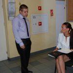Student (stoi) i studentka (siedzi) w oczekiwaniu na egzamin
