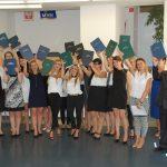 Zdjęcie grupowe studentów po egzaminie dyplomowym w dłoniach uniesione wysoko prace dyplomowe