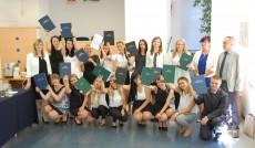 Zdjęcie grupowe studentów po egzaminie dyplomowym, studenci prezentują przed sobą prace dyplomowe, pierwszy rząd kuca