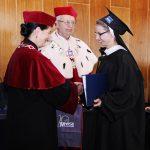 Rektor i Kanclerz wręczają dyplom studentce