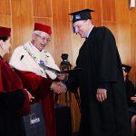 Rektor i Kanclerz wręczają dyplom studentowi