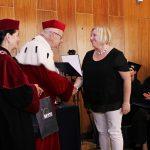 Rektor i Kanclerz wręczają dyplom słuchaczce studiów podyplomowych