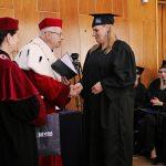 Rektor i Kanclerz wręczają dyplom studentce Beacie Podstawie