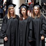 Trzy studentki w togach i biretach stoją na stopniach wiodących do budynku przy ul. Waryńskiego 14