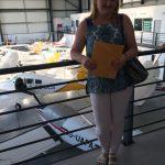 Mgr Ewa Żybura stoi na balkonie hangaru, w dole widoczne samoloty