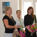 Studentki stoją w sali egzaminacyjnej, trzymają kwiaty