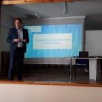 Krzysztof Ostafiński podczas wykładu. W tle prezentacja multimedialna