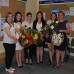 Studentki z bukietami kwiatów w oczekiwaniu na wyniki egzaminu
