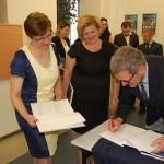 Dr Kazimierz Barwacz wpisuje dedykacje do prac dyplomowych studentów